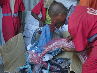 Workers opening one of the cartons containing the bicycle parts.