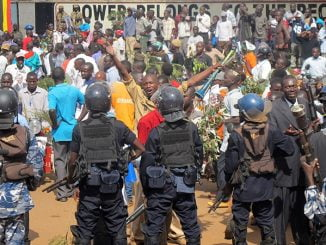 Anti-riot police looks on at protestors in Kampala