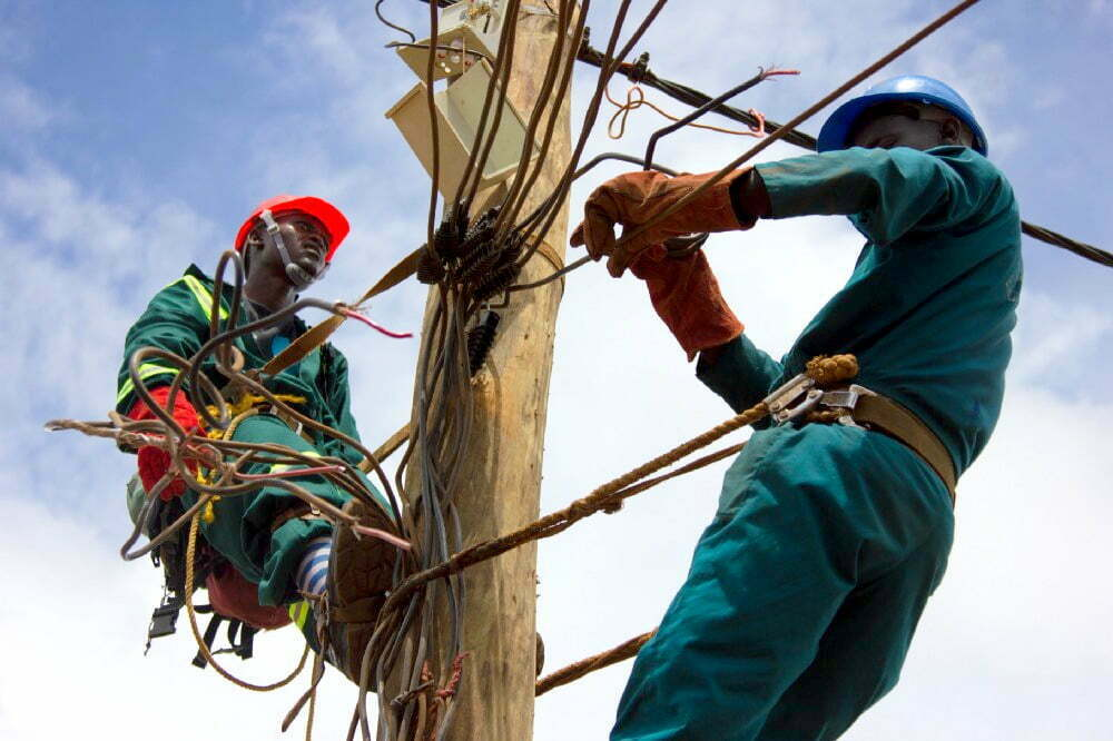 Technicians repair power lines in Kampala.