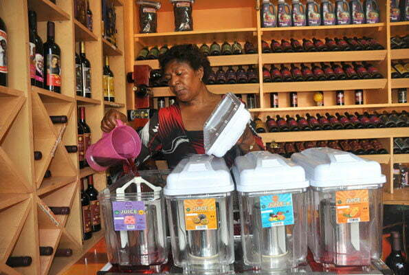 Prudence Ukkonika Busingye displays some of her wine varieties in her shop in Wandegeya