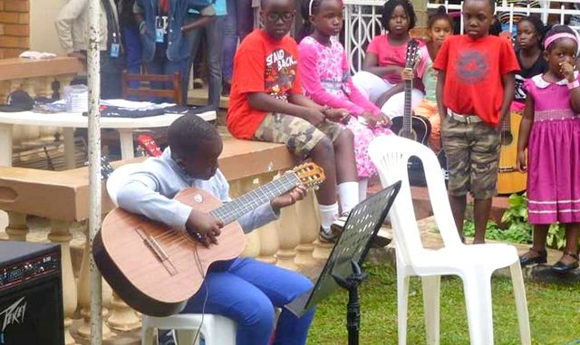 Children practice playing the guitar