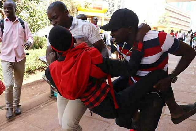 A Makerere University student anti-age limit protester being roughed up by plain-clothes security officers at Parliament today. Courtesy Photo.