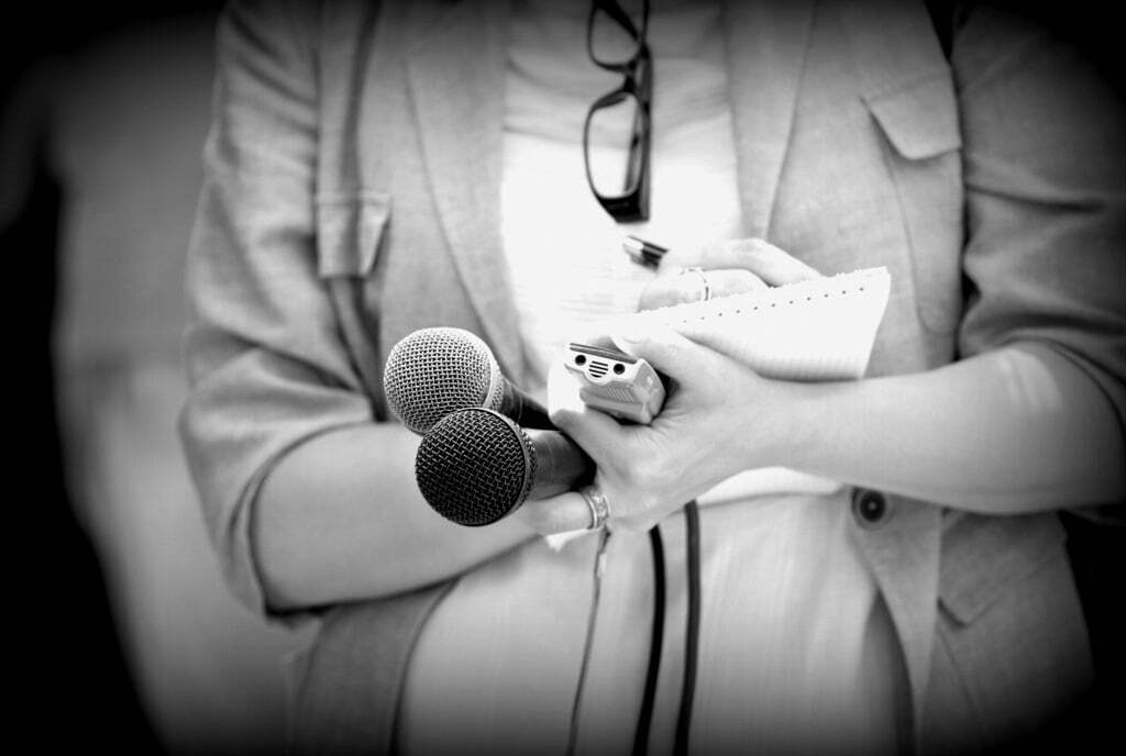 journalist writing in notepad while holding microphones and voice recorder