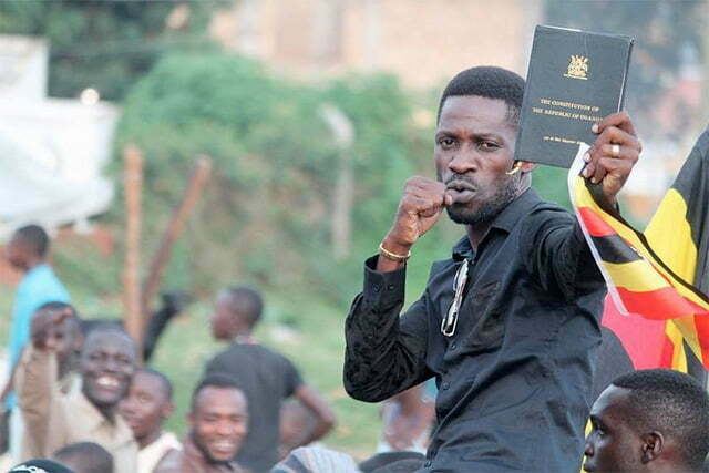 Bobi-Wine-with-a-copy-of-the-constitution-and-Ugandan-flag