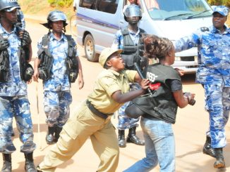 A police officer pushing a journalist as she tried to cover a protestors during the closure of Uganda's newspaper the Daily Monitor in 2013