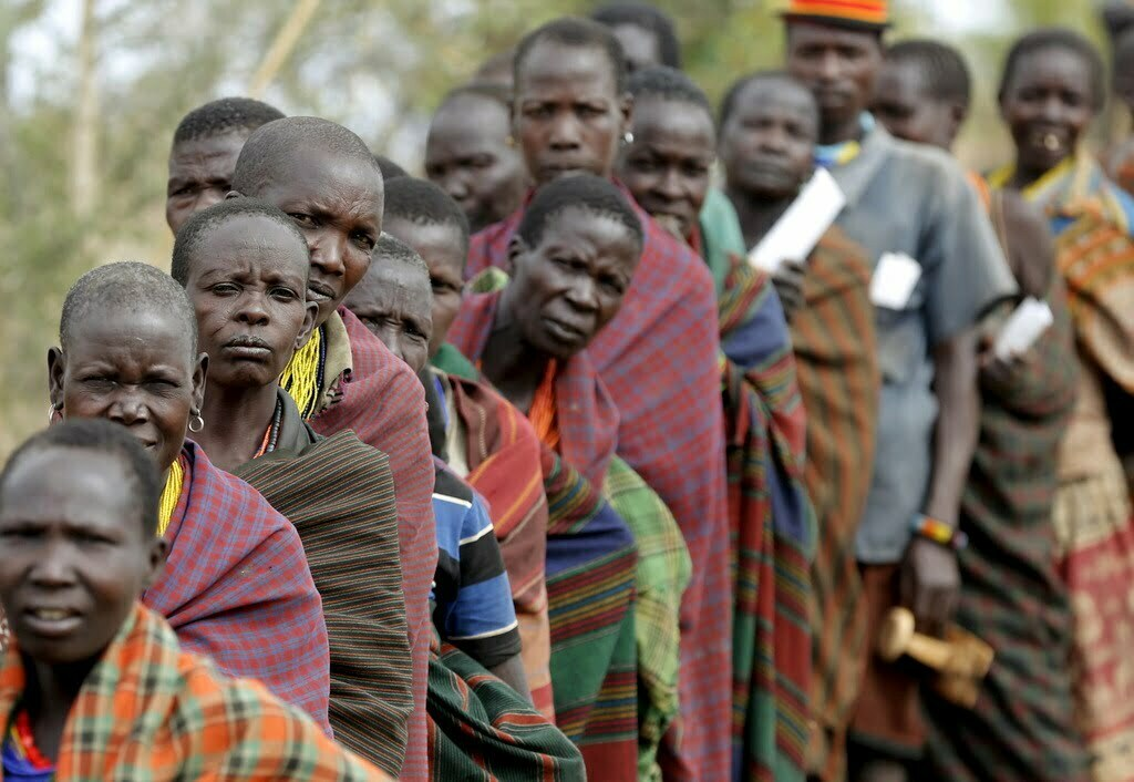 People from Karamojong tribe wait in line to vote at a polling station during elections in a village near the town of Kaabong in Karamoja region