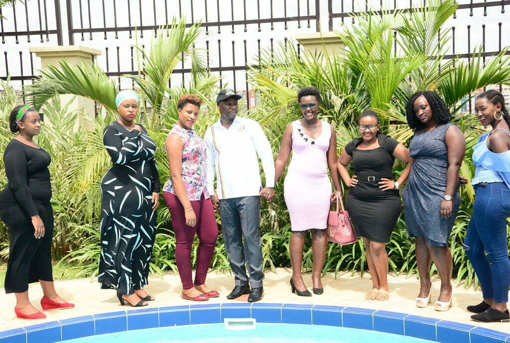 Minister Kiwanda poses with ladies during the launch of Miss Curvy beauty pageant